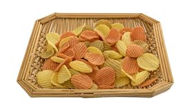 Wicker basket of vegetable chips on a white background. A square wicker basket filled with vegetable chips isolated on a white background Royalty Free Stock Photo