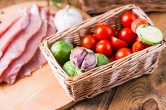 Wicker basket with vegetables and slices of raw  meat. Wicker basket with vegetables and slices of raw meat,pork,chicken,beef,turkey on the wooden table Royalty Free Stock Image