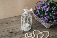Wicker basket with violet flowers and beautiful white pearl necklace on a wooden background. Royalty Free Stock Photo