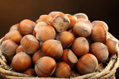 Wicker basket with walnuts on a brown background Royalty Free Stock Photos