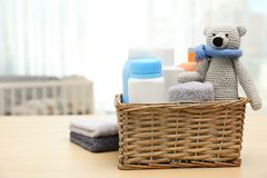 Free Wicker Basket With Baby Cosmetic Products, Toy And Towels On Table Indoors. Stock Photo - 145025780