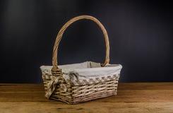 Wicker basket on wooden table. Wicker basket on wooden board and black background stock photo