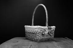 Wicker basket on wooden table. Wicker basket on wooden board and black background stock image