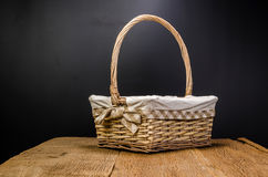 Wicker basket on wooden table. Wicker basket on wooden board and black background royalty free stock photos