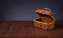 Wicker basket, wooden table Stock Photos
