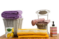 Wicker baskets full of clean colored towels. Wicker basket full of clean colored towels on a wooden table in a bathroom set stock images