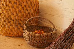 Wicker baskets. Inside of a wooden cottage: a wicker baskets and a broom Stock Images