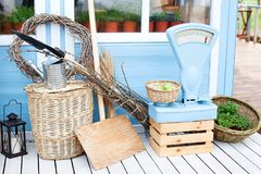 Wicker baskets next to the garden equipment against the wall of a blue country house. Summer seasonal vacation. Garden plants in p. Ots. Gardening. Spring Garden royalty free stock images