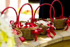 Wicker baskets with red ribbons with red and white petals of roses Stock Photos