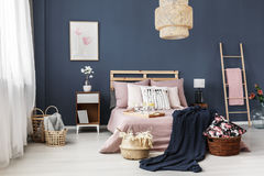 Wicker baskets in room. Small decorative wicker baskets in a room with big wooden bed stock photos