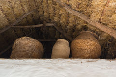 Wicker baskets under a thatched roof Stock Photos