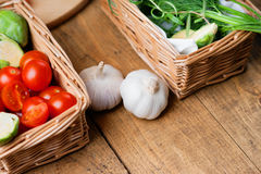 Wicker baskets with vegetables and garlic on a wooden background Stock Image