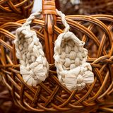Wicker bast shoes on a wooden basket, Russian amulet stock photography