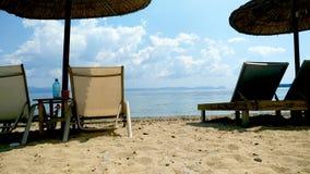 Wicker beach umbrellas and sun loungers on stunning sandy beach, blue sky with few clouds, Halkidiki Greece