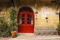 Wicker bench red door Saint-Cyprien Dordogne Royalty Free Stock Photography
