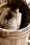 Wicker bottles. Wicker bottle of wine in an old empty barrel. Sepia Stock Photography