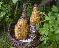 Wicker bottles. On green grass Stock Photography