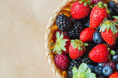 Wicker bowl with assortment berries blueberries, strawberries, raspberries and blackberries. Rustic style. Top view. With place for your text, for background Royalty Free Stock Photography