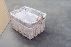 Wicker box of rattan Boho type, with handles on the concrete floor. stock photo