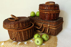Wicker boxes and green apples. Wicker from a vine basket with apples on a white background Royalty Free Stock Photography