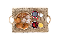 Wicker Breakfast Tray on White Background. High Angle View of Wicker Breakfast Tray with Assortment of Breads and Berries, Coffee, Juice and Hard Boiled Egg on Stock Photography