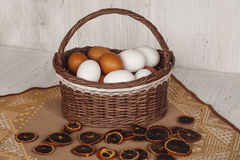 Wicker brown basket with eggs in cozy background.  stock images