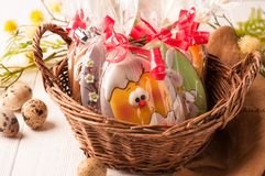 Wicker brown basket with wrapped easter cookies near quail eggs and blossoming branch stock images