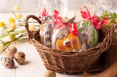 Wicker brown basket with wrapped easter cookies near quail eggs and blossoming branch stock photo