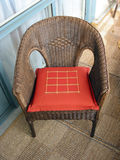 Wicker chair. Brown wicker chair with red cushion Stock Photos