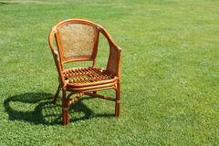 Wicker chair on the background of fresh grass Stock Photography