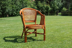 Wicker chair on the background of fresh grass Stock Photos
