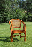 Wicker chair on the background of fresh grass Stock Images