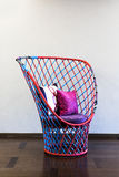 Wicker chair in front of a plain wall Stock Photo