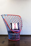 Wicker chair in front of a plain wall Royalty Free Stock Photos