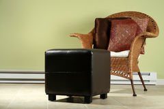 Wicker chair and ottoman. Ceramic tile flooring with ottoman and comfortable wicker chair Stock Photos