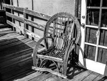Wicker Chair on Porch. Weathered wicker rocker on old wooden porch in black and white Royalty Free Stock Photography