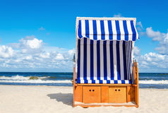 Wicker chair on sandy Kolobrzeg beach, Baltic Sea, Poland Stock Photos