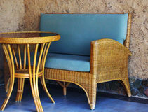 Wicker chair and table. Wicker table and chair with blue cushion on patio stock images