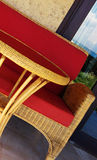 Wicker chair and table. Wicker table and chair with red cushion on patio stock photos