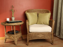 Wicker chair and table. Pleasing wicker furniture set against a red wall with a green drape and wood flooring Stock Photo