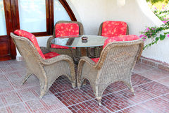 Wicker chair and table outdoors Stock Photos