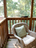 Wicker chair on veranda. Comfortable wicker chair on wooden veranda with trees in background Stock Photo