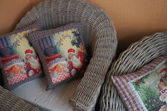 Wicker chairs, cushions with Christmas pictures. Interior, decorative, wooden, design, home furniture royalty free stock photos