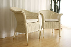 Wicker chairs indoors. Two wicker chairs on wooden floor Stock Images