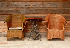 Wicker chairs and new design table. Wicker chairs and the sophisticated table (made from sewing machine) encourage to relax Royalty Free Stock Images