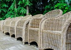 Wicker chairs in a row in the park stock images