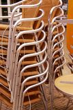Wicker Chairs Stacked Outside. A stack of wicker and metal chairs outdoors Royalty Free Stock Photos