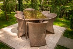 Wicker chairs and table are in the garden near trees. royalty free stock photos