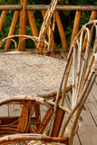 Wicker Chairs And Table Profile. Two rustic whicker chairs set up on a wooden deck stock images