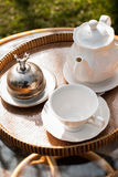 Wicker chairs and table with tea set Stock Photos